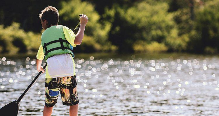 Barn med flytväst vid vatten.