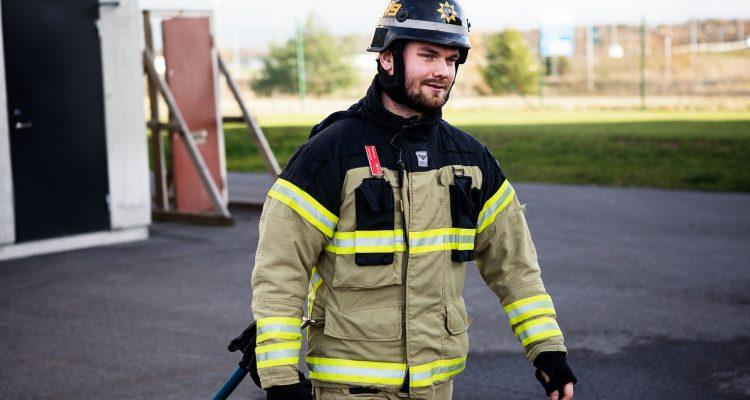 En manlig brandman med hjälm bär en brandslang.