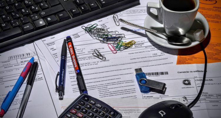 Bild på rörigt skrivbord med en massa pappersfakturor på.