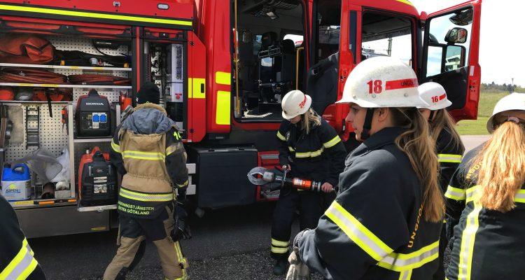 Fyra kvinnor i brandmanskläder framför en brandbil.