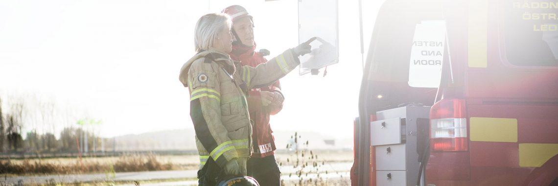 En brandman och en insatschef står bredvid en stor röd bil och pekar på en tavla med information om en pågående insats.
