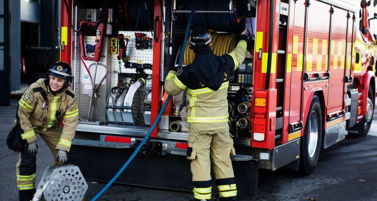Två brandmän jobbar vid baksidan på en brandbil.
